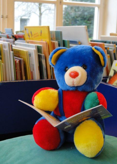 Ein bunter Bär liest in der Kinderbücherei ein Bilderbuch.